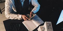 Canva - Person Counting Money With Smartphones in Front on Desk